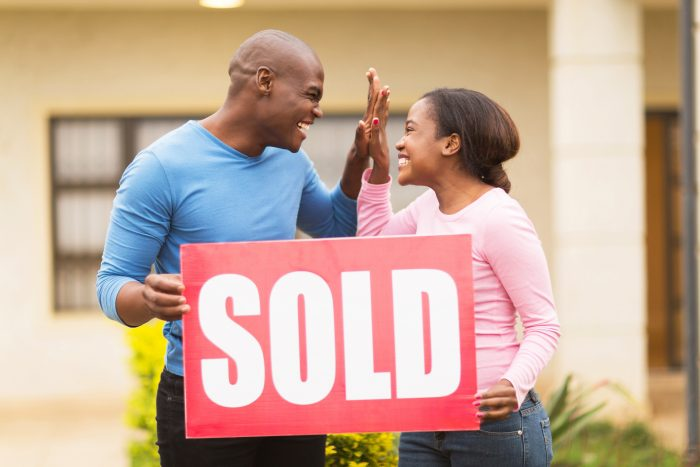 Couple high fives while buying a house